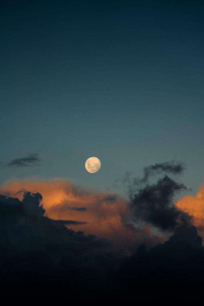 moon among fluffy clouds on a dusky evening